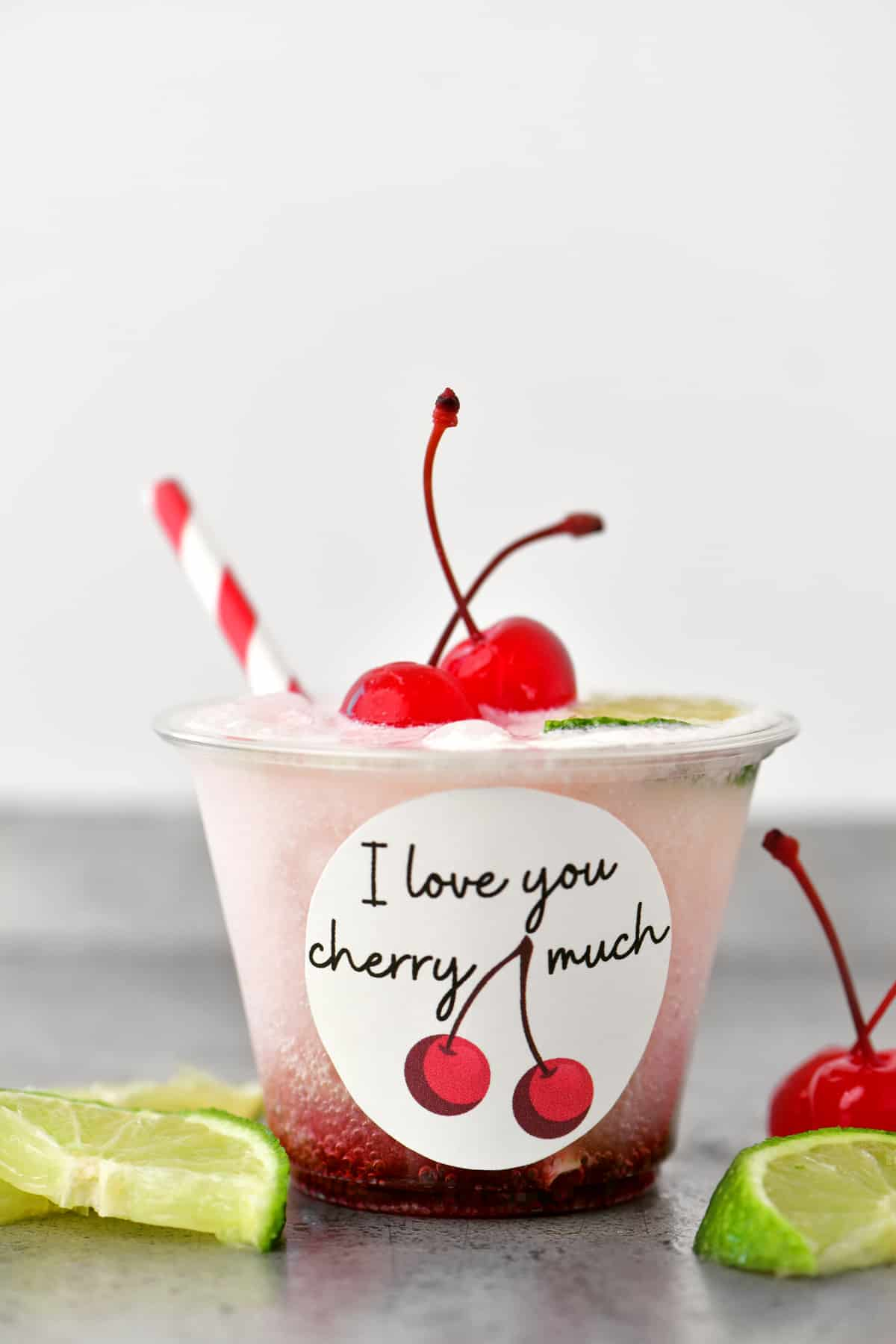 a cherry flavored valentines drink in a clear cup with a red and white striped straw