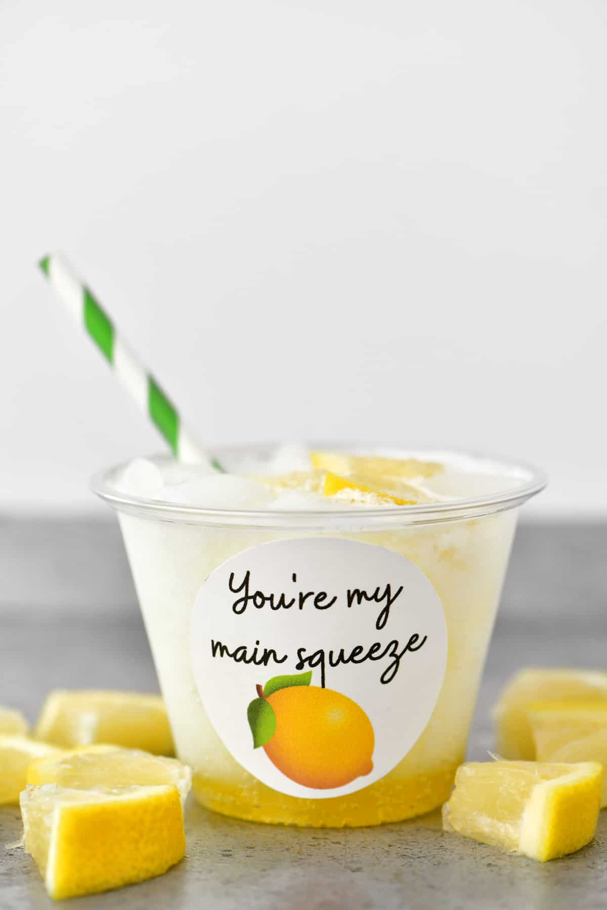 a lemon flavored valentines drink in a clear cup with a green and white striped straw
