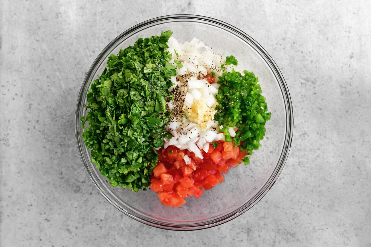 Cilantro, diced tomatoes, diced onions, garlic and other pico de gallo ingredients in a glass bowl