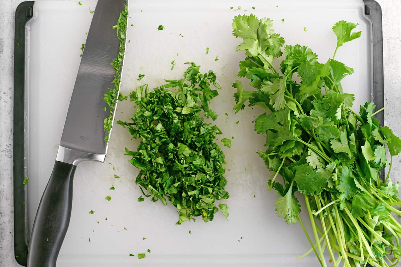 a knife and chopped cilantro on a cutting board