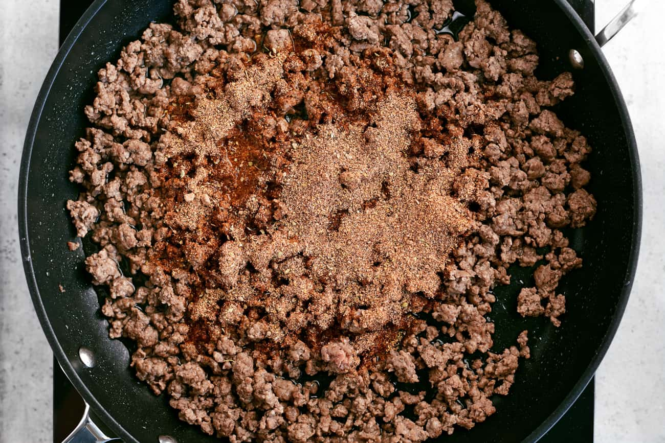 seasonings and meat in a frying pan
