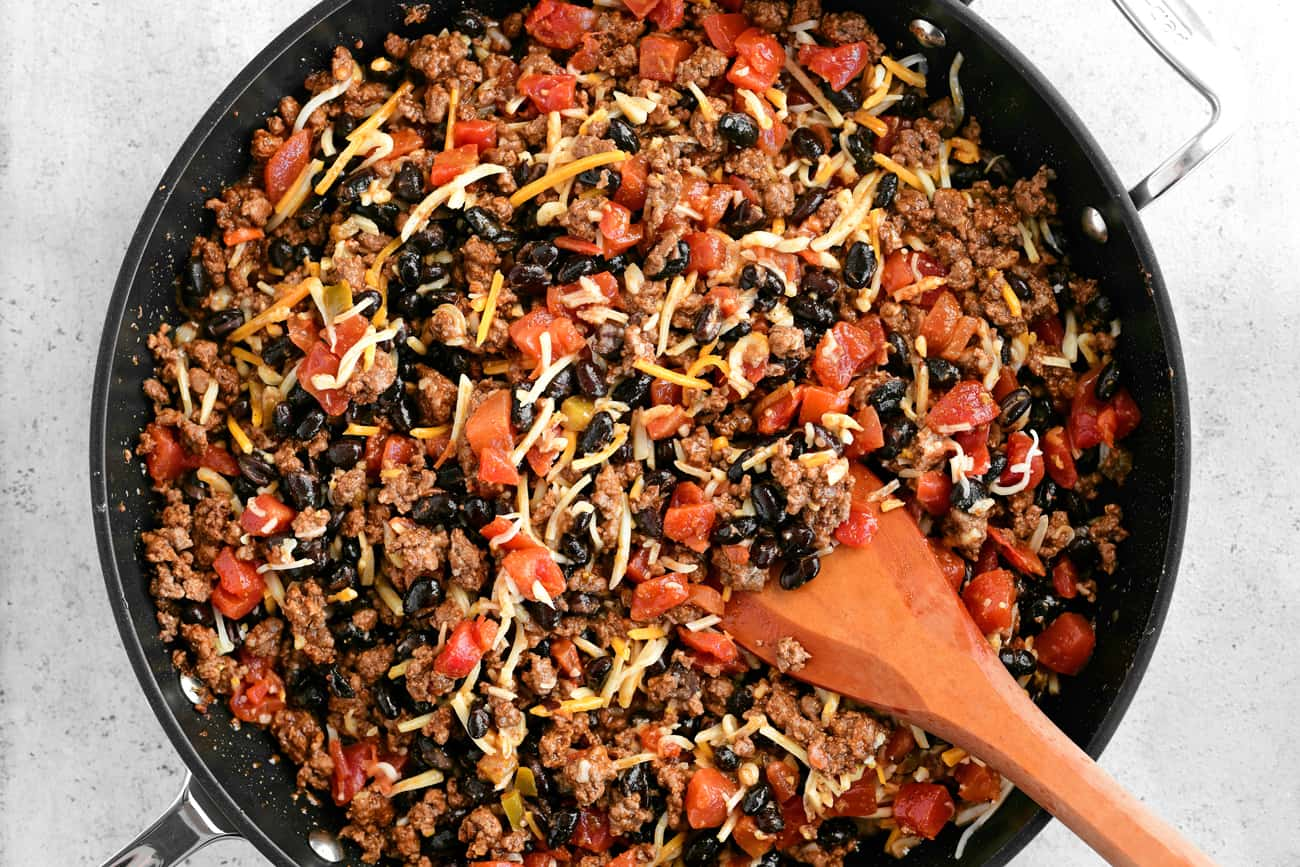 hamburger peppers beans and tomatoes in a pan