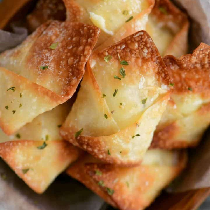 golden colored wontons in a wooden bowl