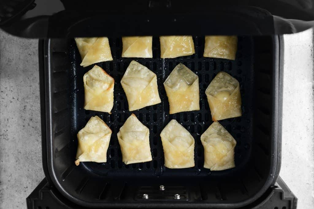 wontons cooking in an air fryer