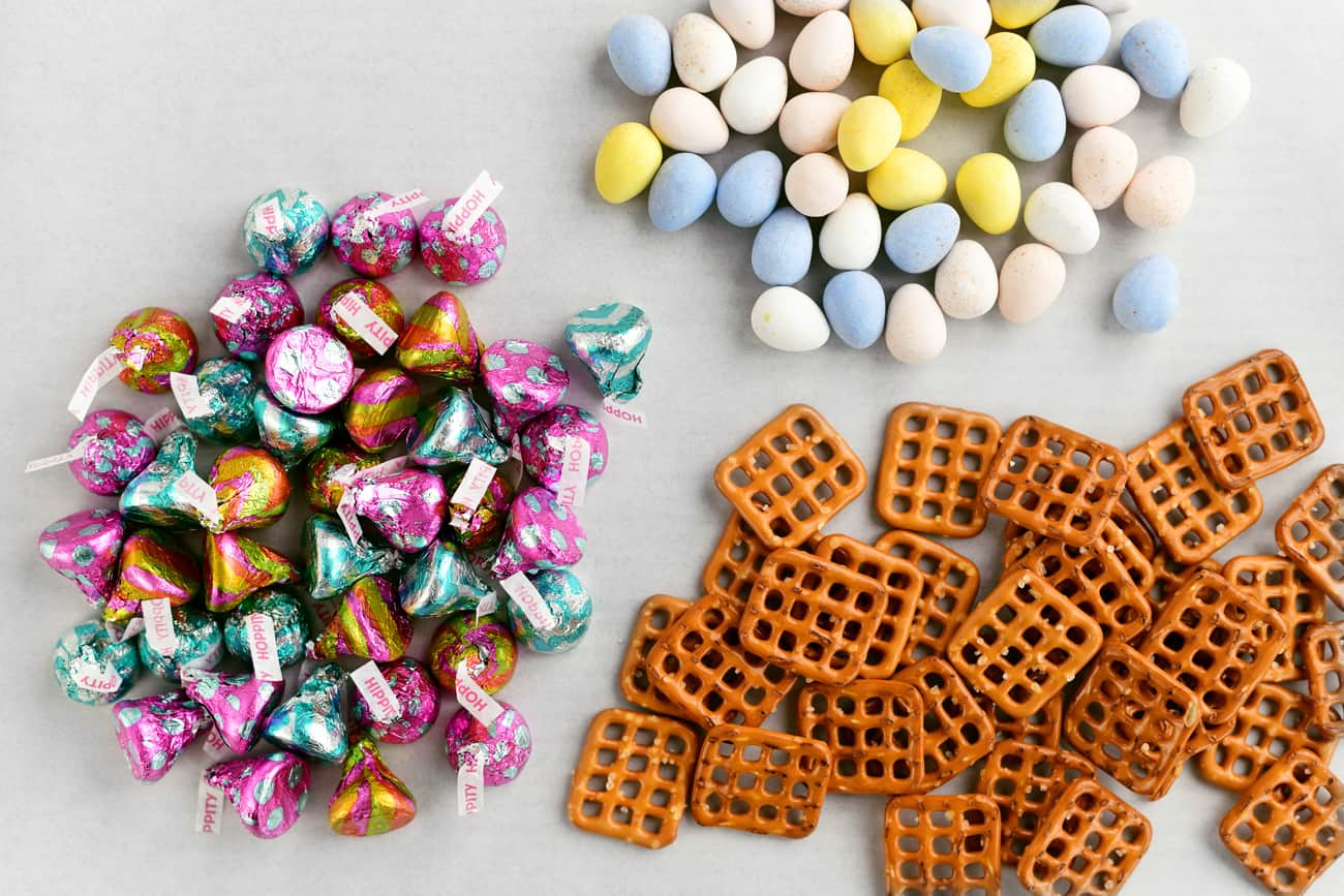 pretzel squares, Cadbury Mini-Eggs, and Hershey Kisses in piles on a cutting board