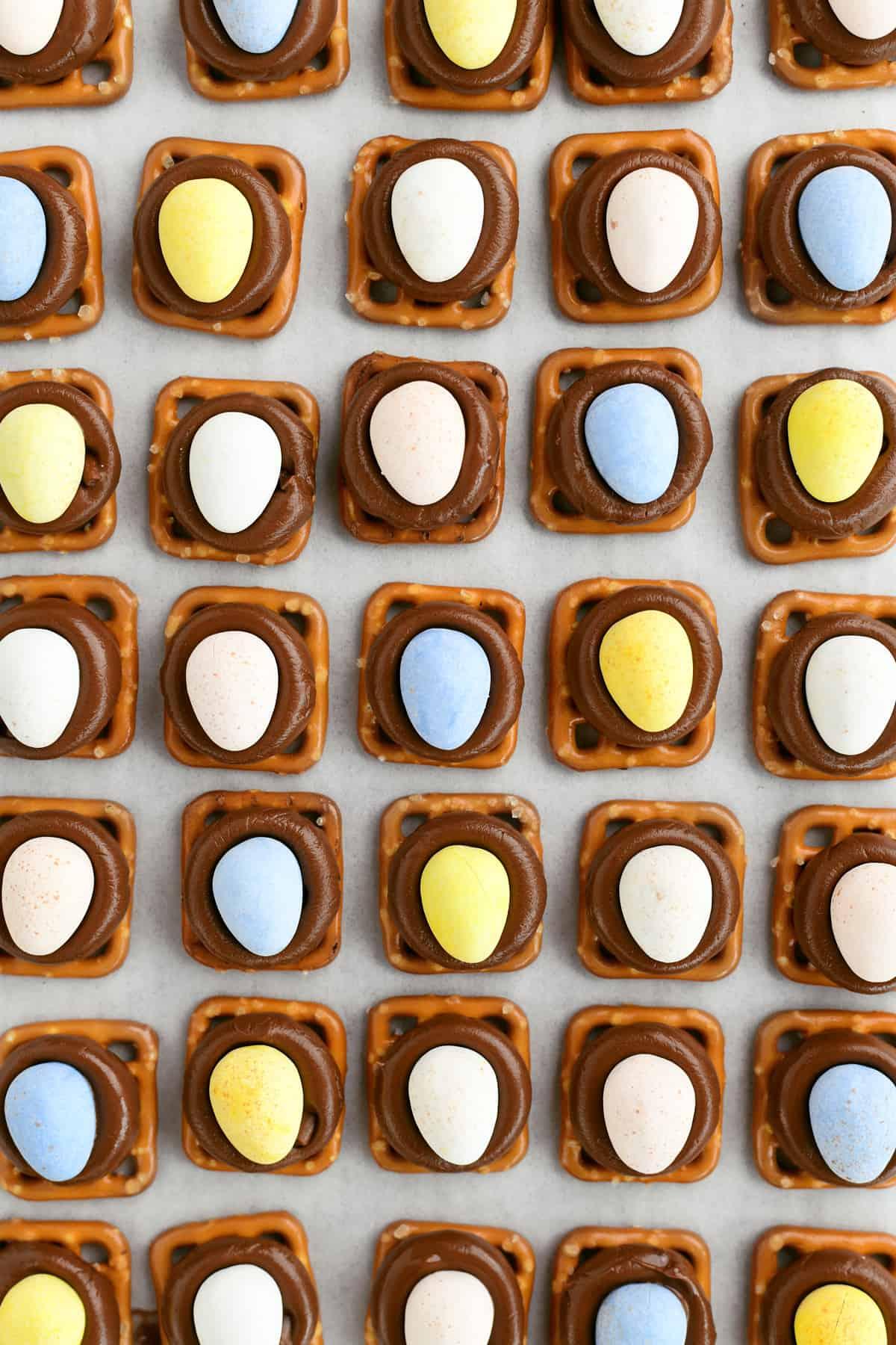 Colorful Cadbury-Mini-Eggs-pressed into Hershey Kisses on pretzels