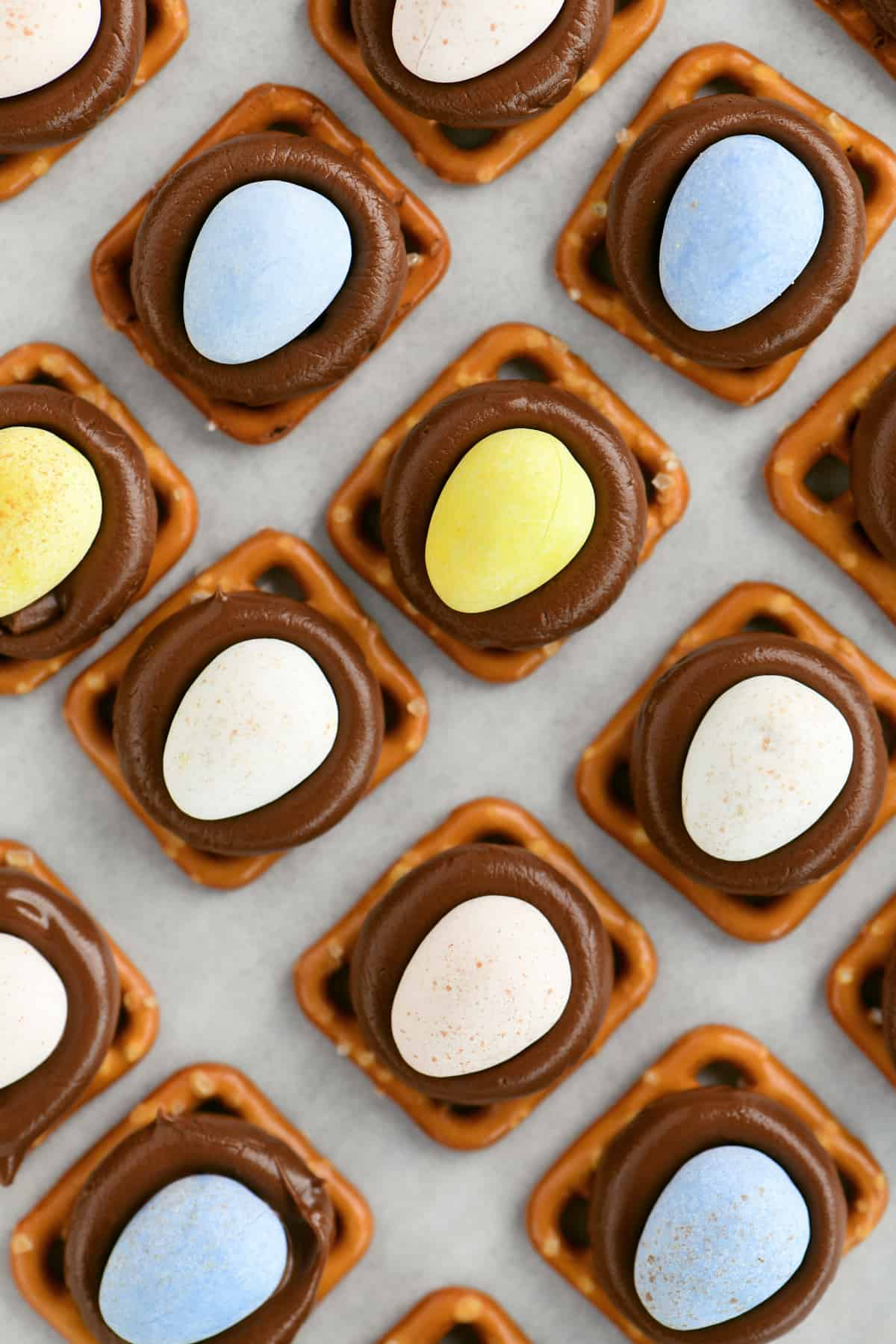 yellow blue and white candy eggs on chocolate kisses on top of pretzel squares