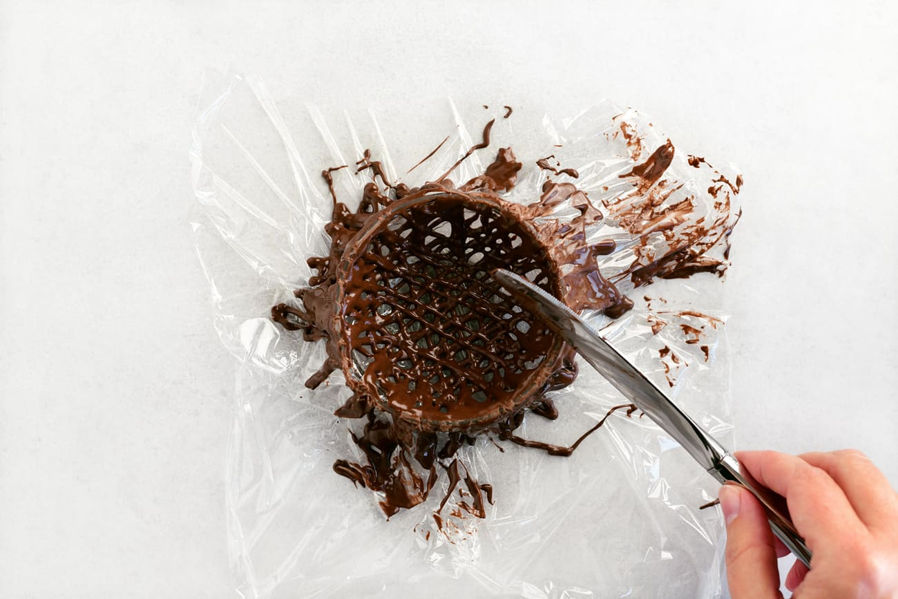 scraping the edge of the chocolate nest before removing it from the bowl