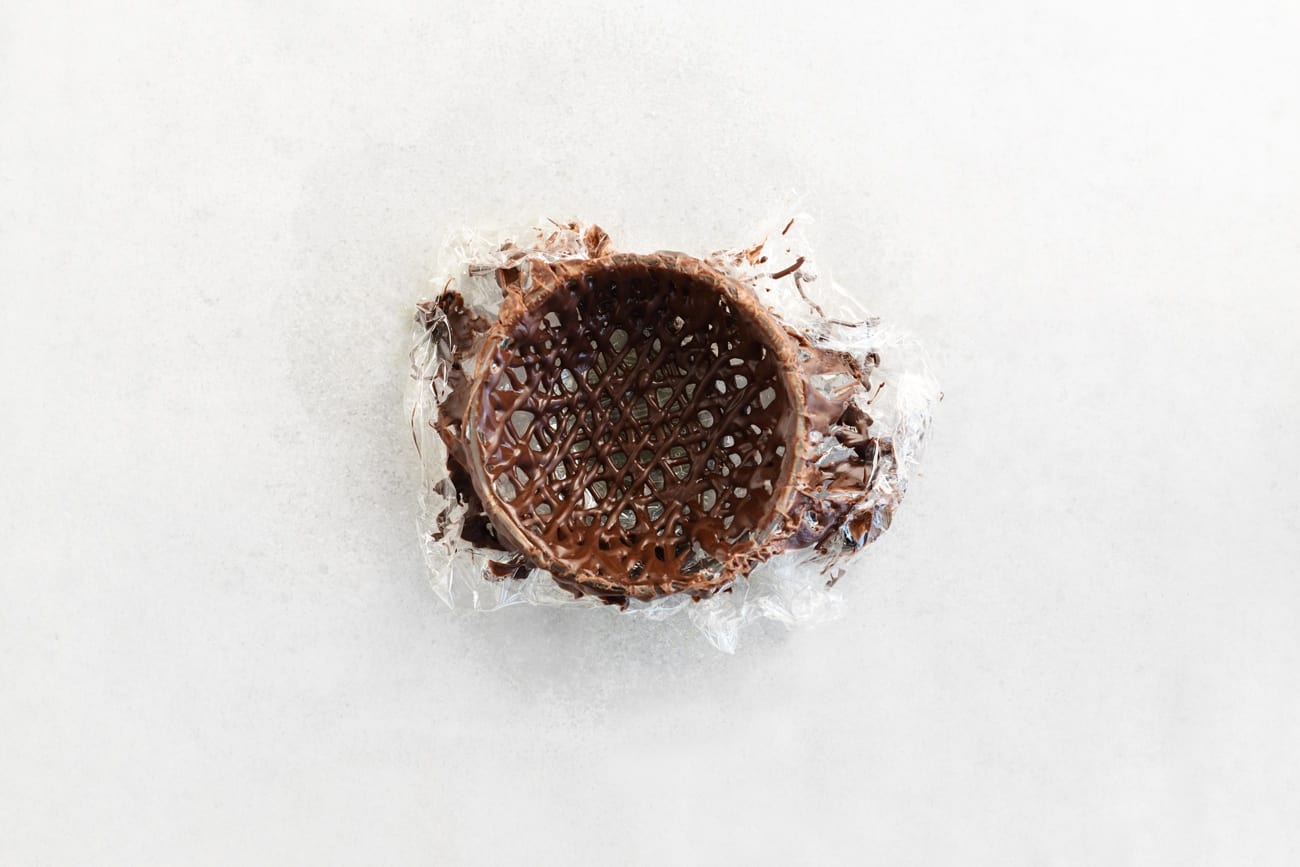 a chocolate nest ready to be released from the plastic covered bowl