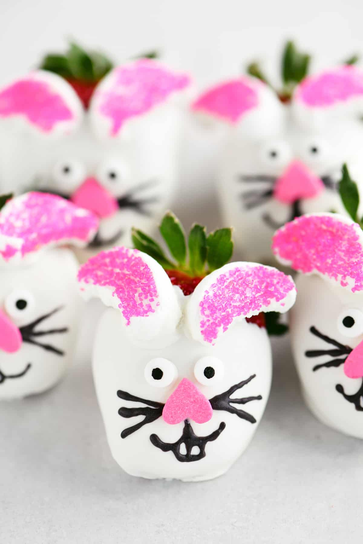 easter bunny dipped strawberries lined up on a sheet of parchment paper