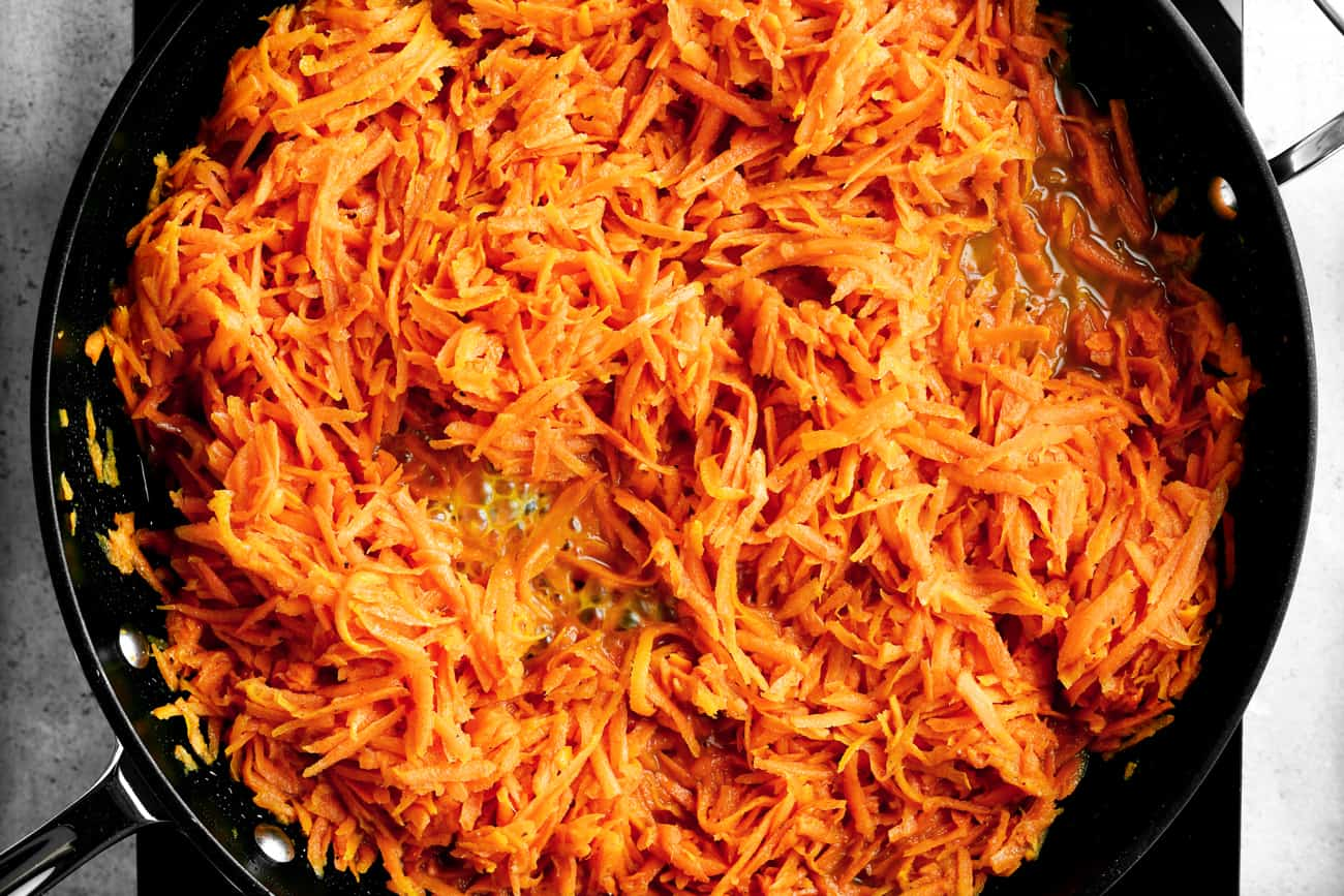shredded carrots in a frying pan with glaze mixture