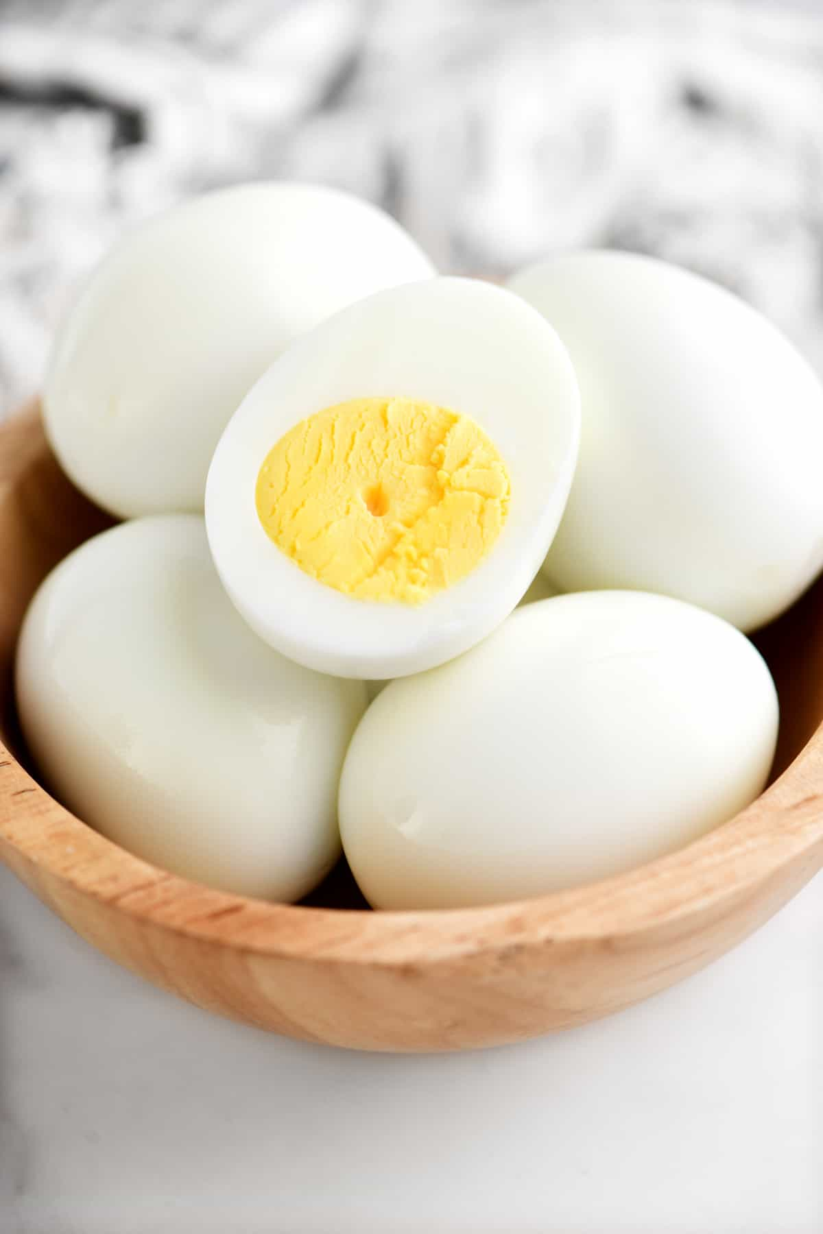 hard boiled eggs in a bowl, one is cut in half