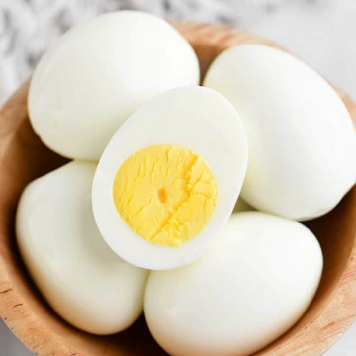 boiled eggs in a bowl, one egg is cut in half so you can see the yolk