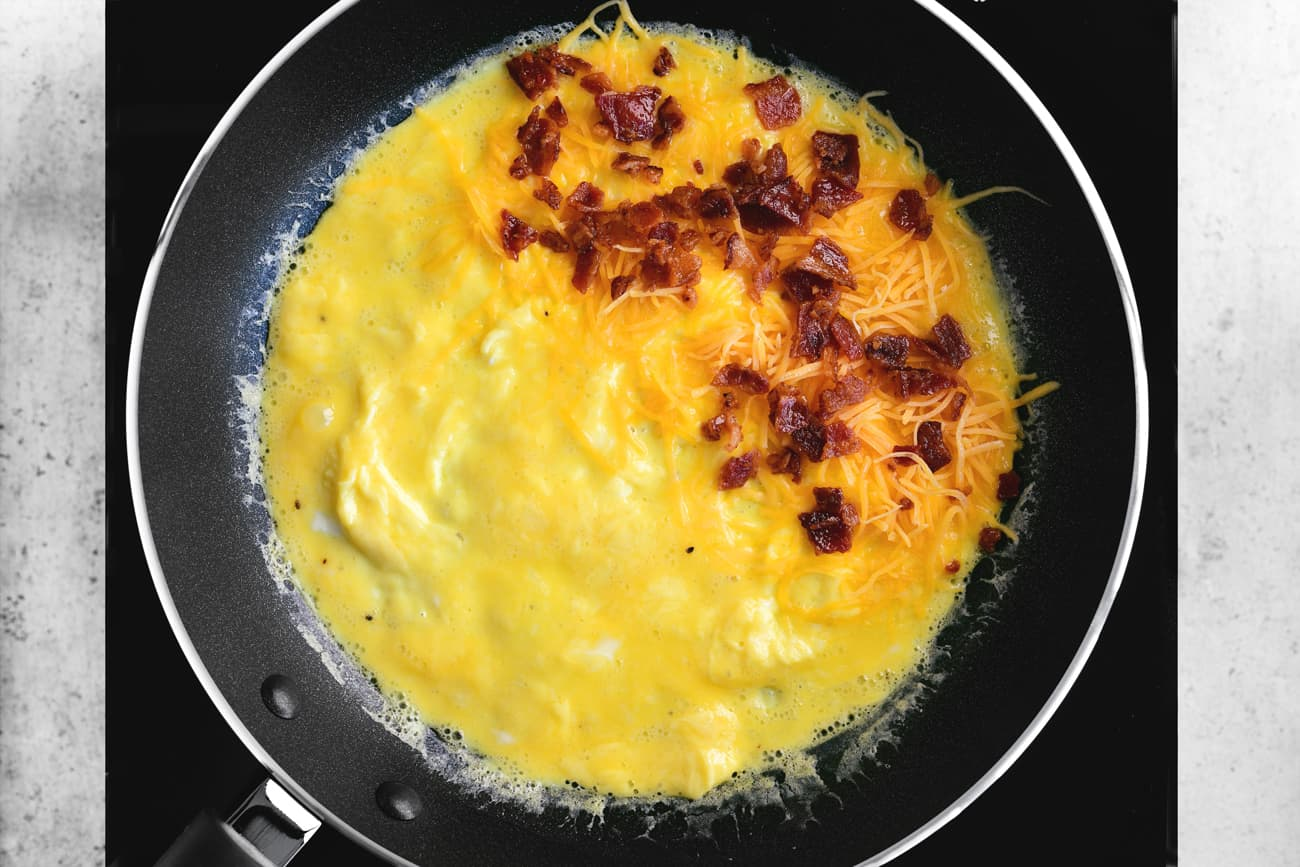 bacon bits added to the omelet in a skillet