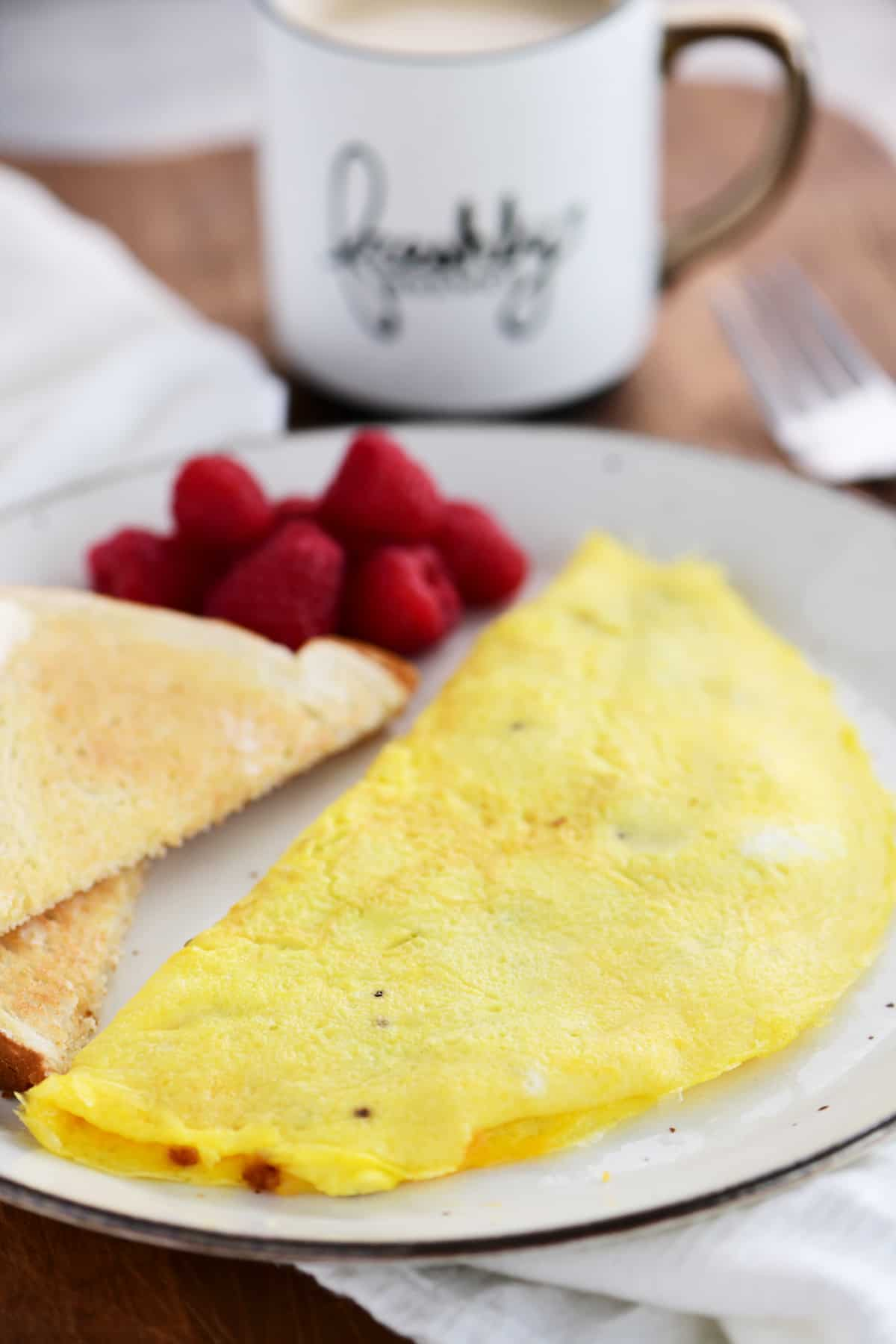 an omelet, toast and raspberries on a plate