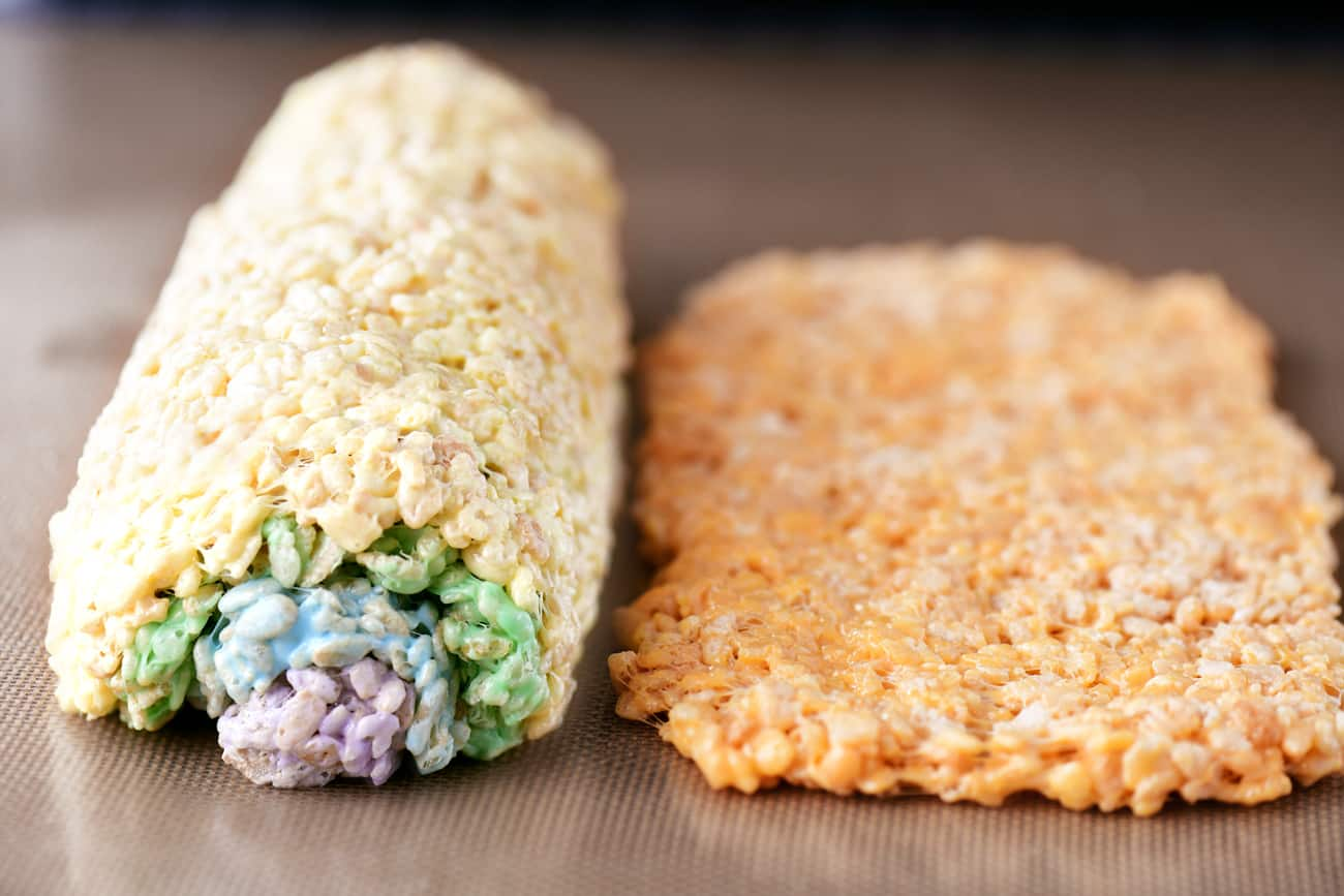 an orange layer of rice krispie treats rolled out flat next to the multi colored roll of rice krispies