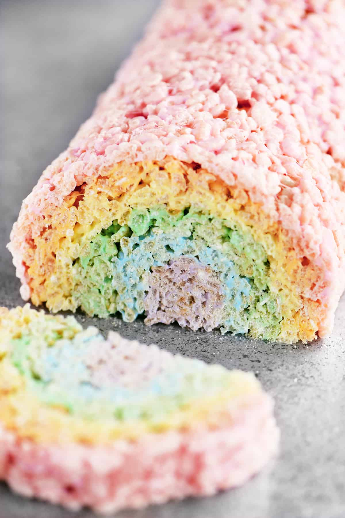 a slice of rainbow rice krispie treats laying next to the roll it was cut off of