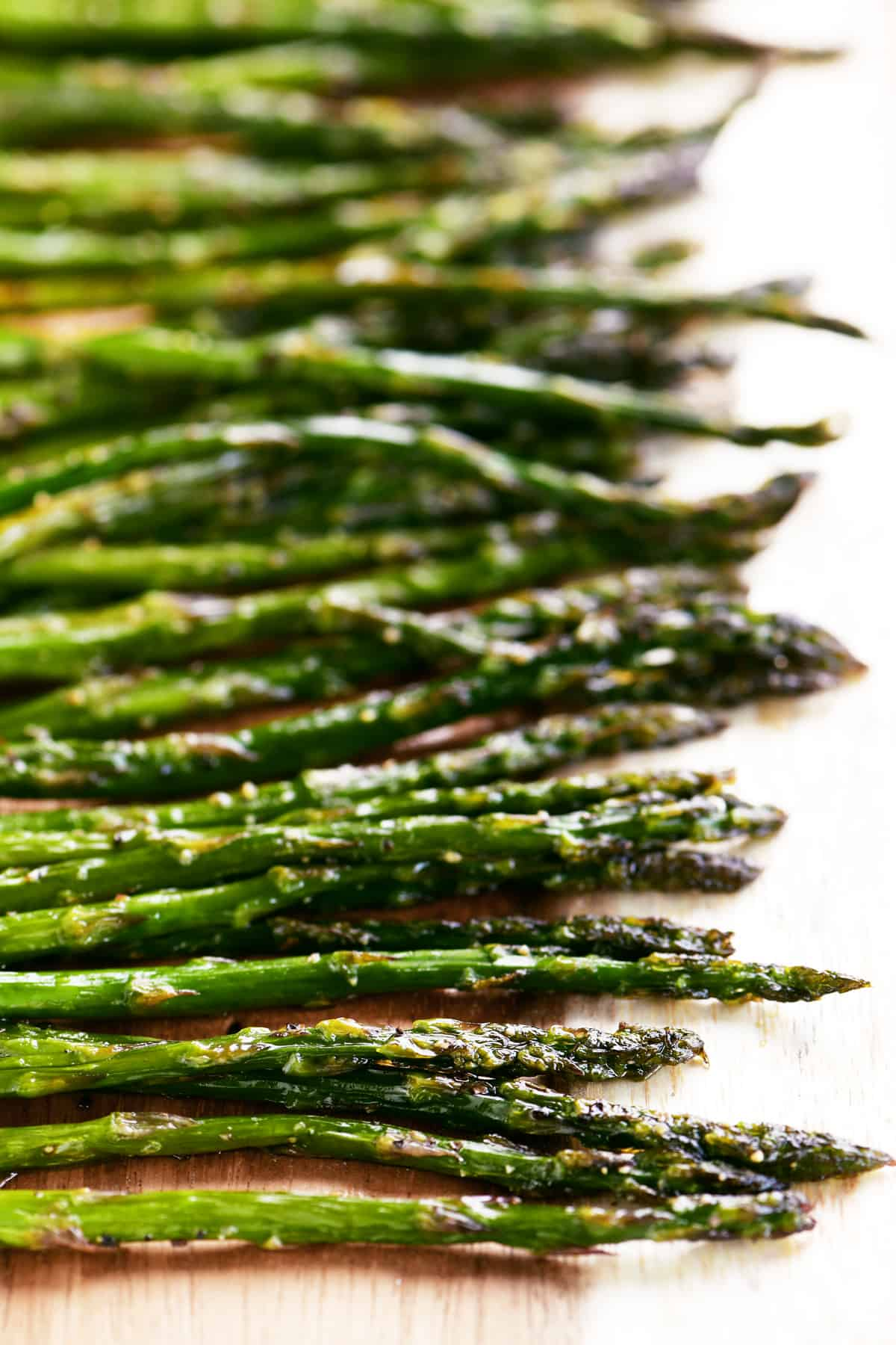 cooked asparagus on a wood board