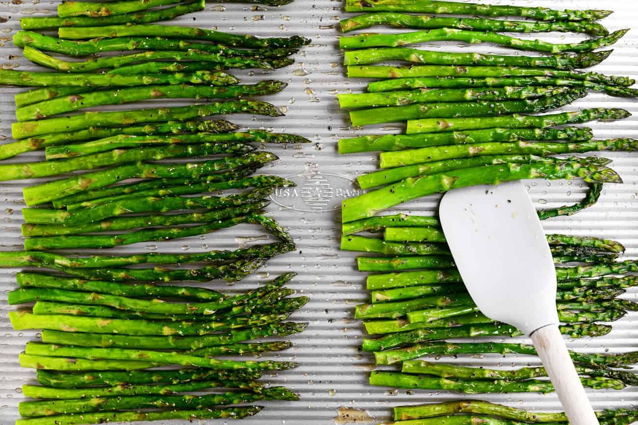 a spatula and asparagus on a metal pan