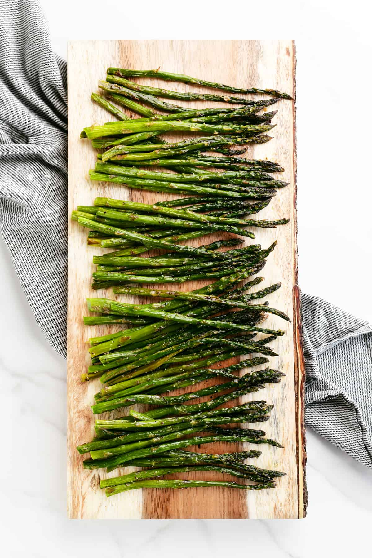 a wooden cutting board with roasted asparagus on it