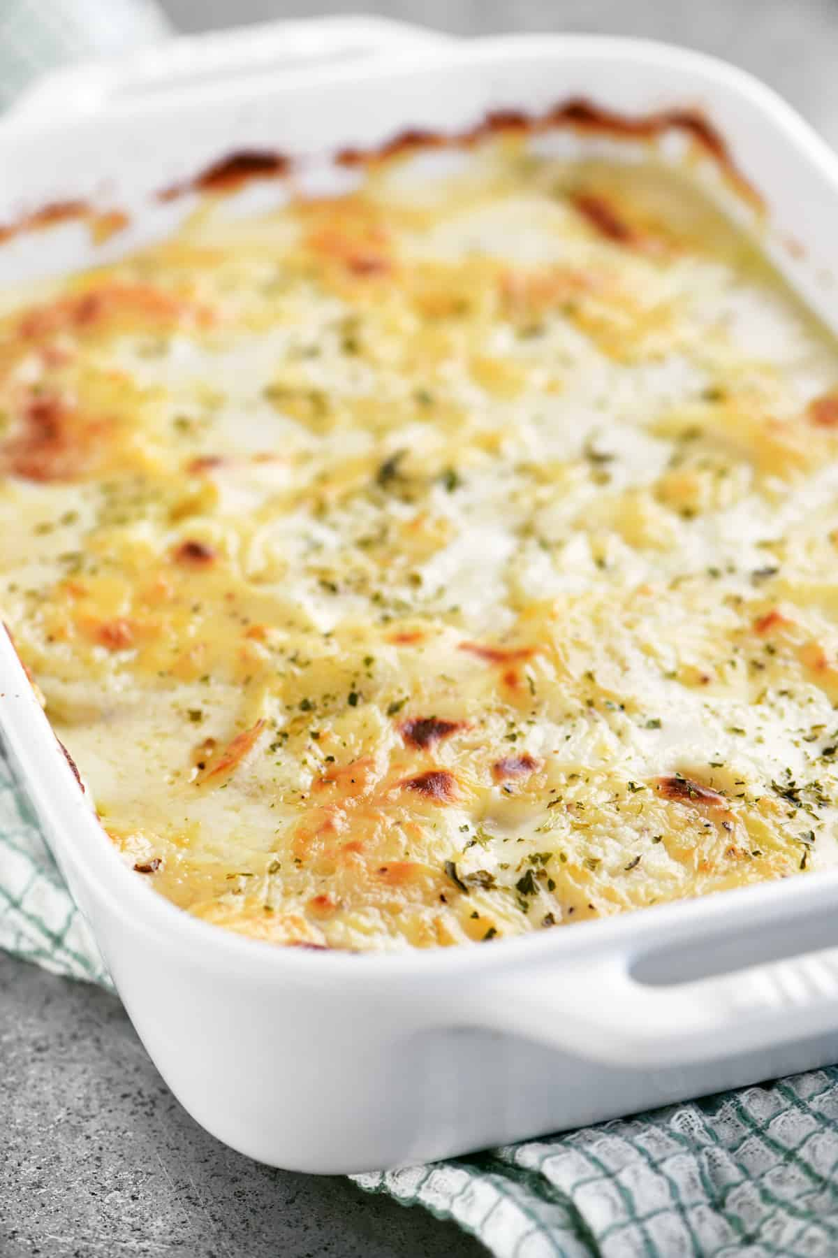 baked scalloped potatoes in a white baking dish
