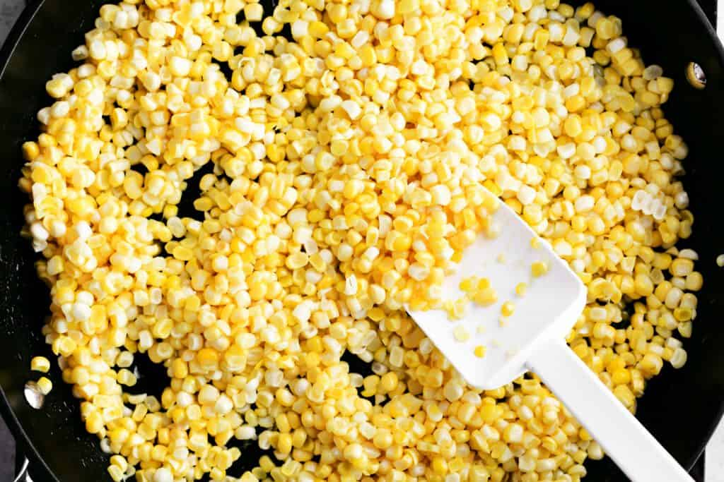 a white spoon-shaped spatula and uncooked kernels of corn in a frying pan