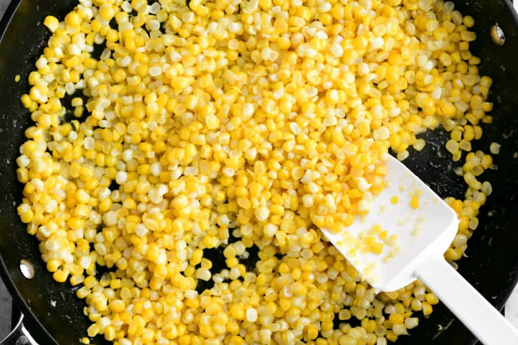 a white spoon-shaped spatula and cooked kernels of corn in a frying pan