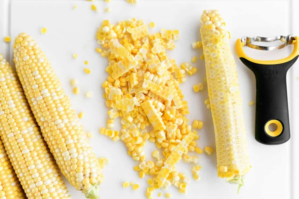 a corn peeler tool and peeled corn kernels on a cutting board along with a few unpeeled cobs of corn