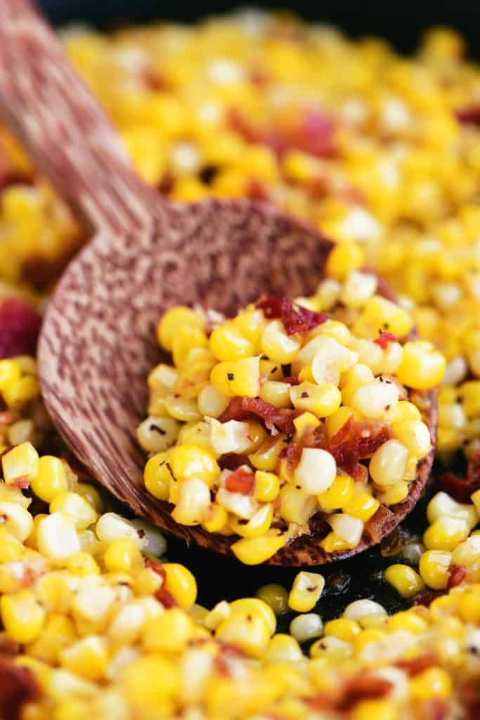 a wooden spoon with peppered corn and bacon in it