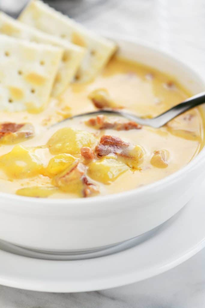 a spoon and 3 crackers in a bowl of ham and potato soup