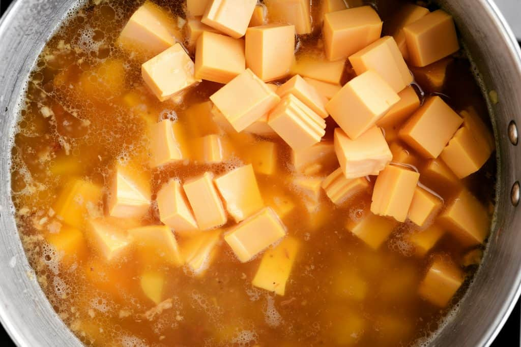 cubed cheddar cheese in the soup broth in a large pot