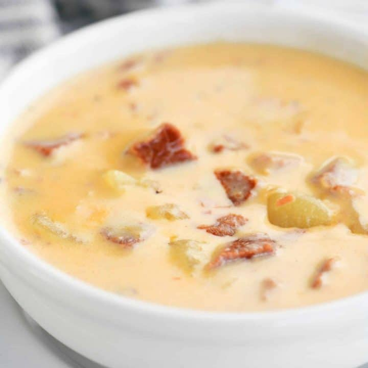 cheesy ham and potato soup in a white bowl
