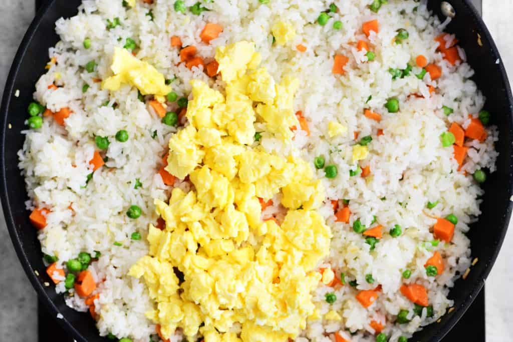 scrambled eggs added to rice mixture in pan