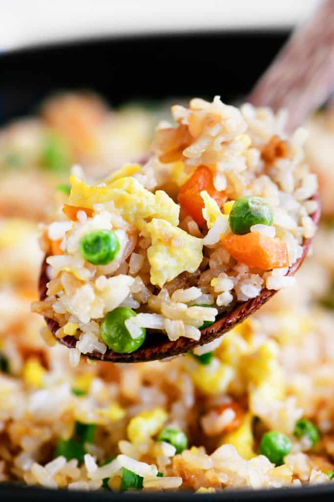 spoonful of fried rice with carrots and peas
