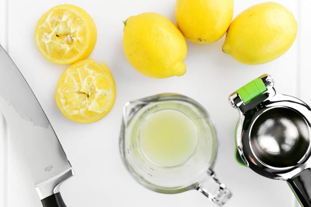 lemons, lemon juice, a knife and a citrus squeezer