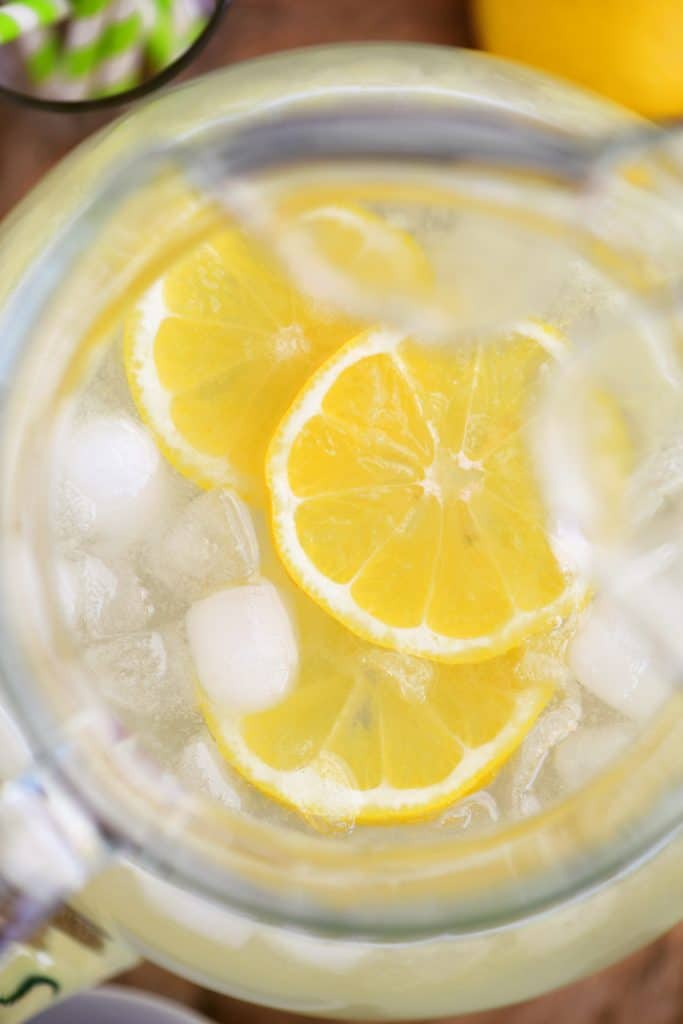 lemon slices floating in pitcher with ice cubes