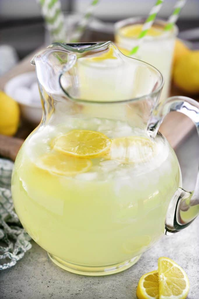 a glass pitcher with lemonade, lemon slices, and ice cubes