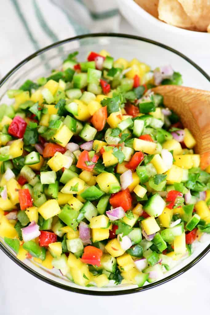 topdown view of mango salsa in a bowl with a wooden spoon