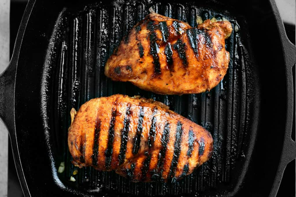 two chicken breasts grilling in cast iron grill pan