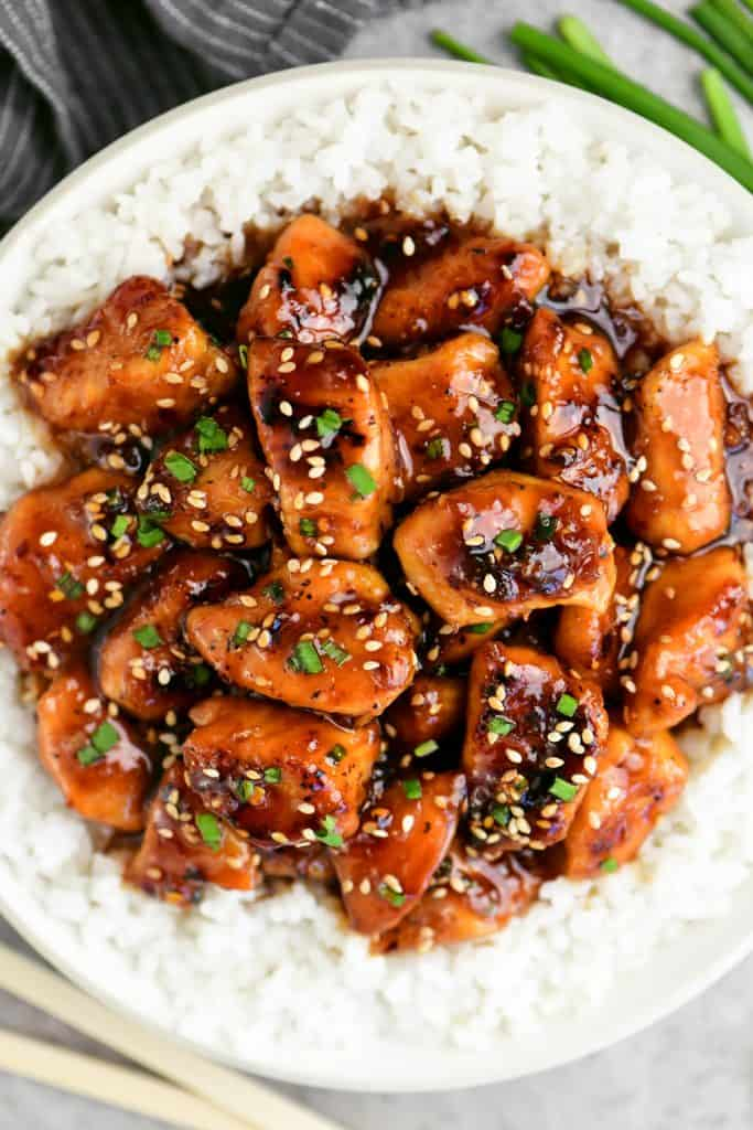 white bowl with sesame chicken and white rice