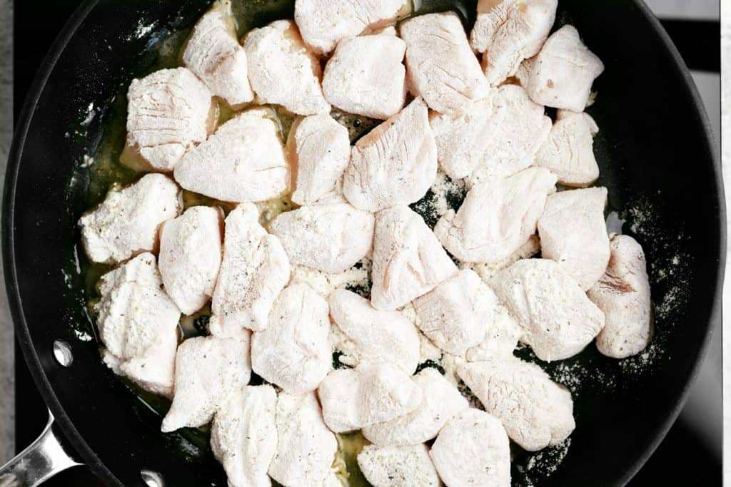 flour coated chicken in a pan