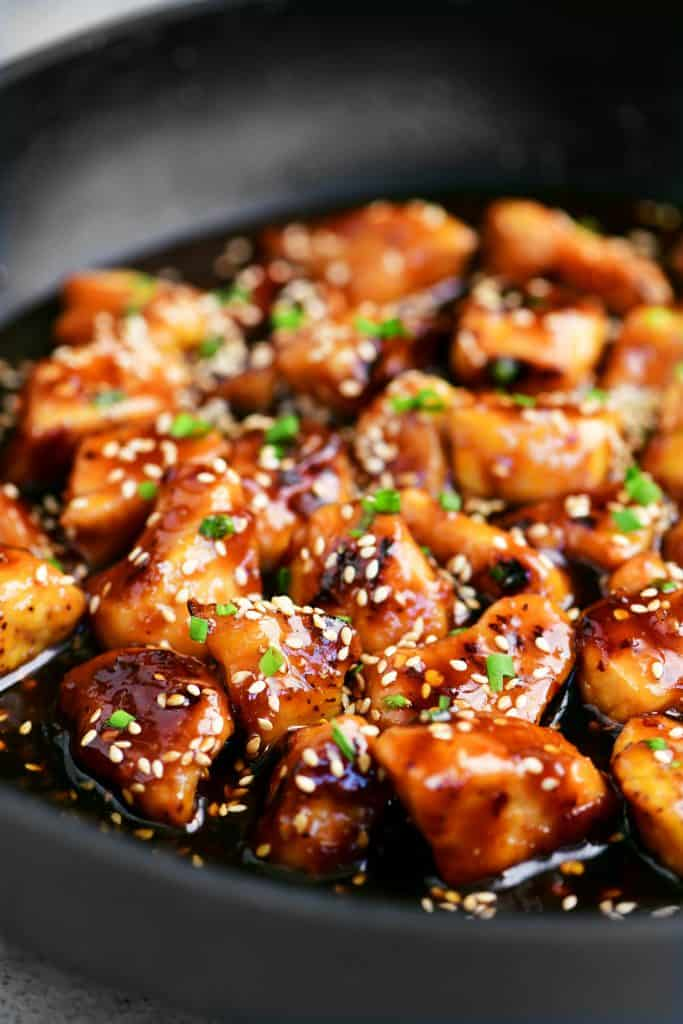 sesame chicken in a skillet with chives on top