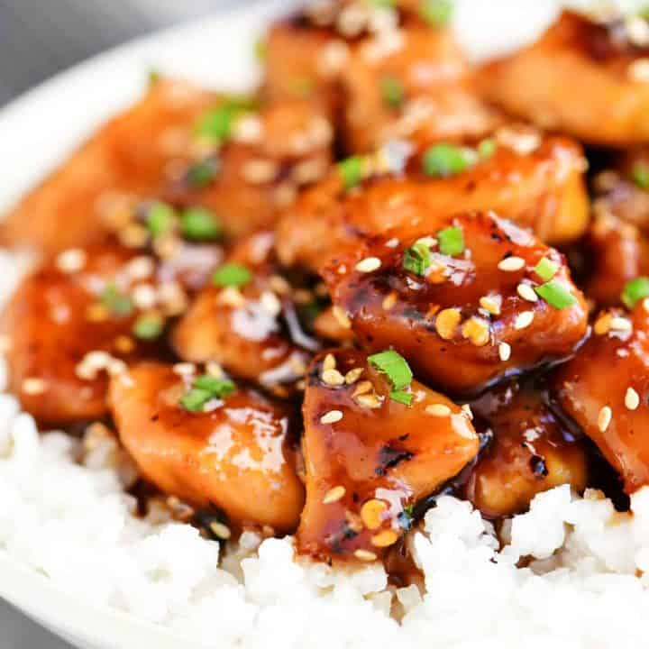 sesame chicken in a bowl with white rice