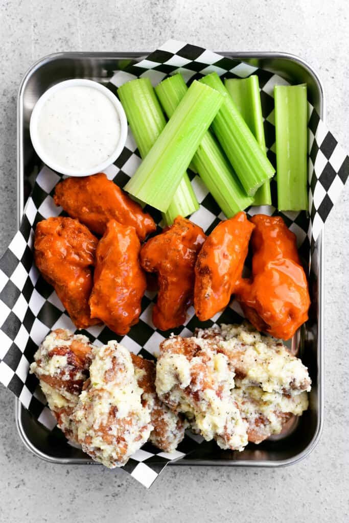 a food tray with 11 chicken wings and 6 pieces of celery and sone dipping sauce inside