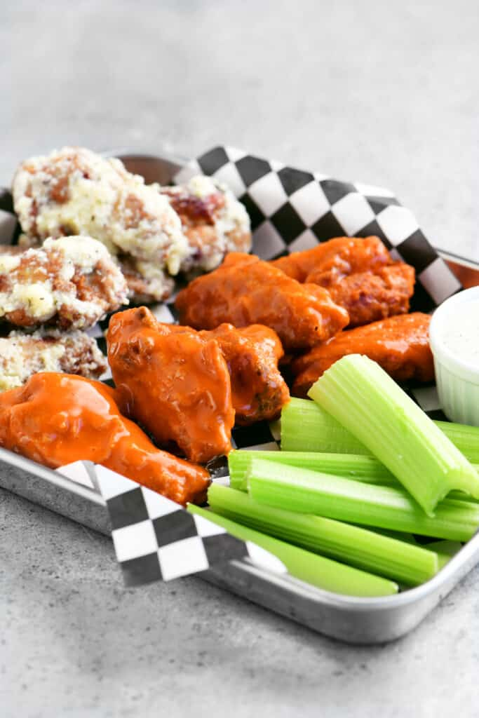 a stainless tray with buffalo wings and parmesan garlic wings and celery