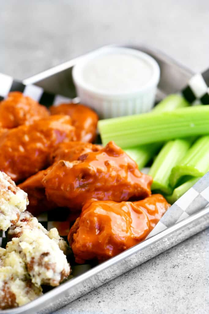 chicken wings with buffalo sauce and celery on a tray