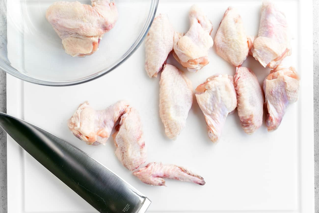 a knife and uncooked chicken wings on a cutting board