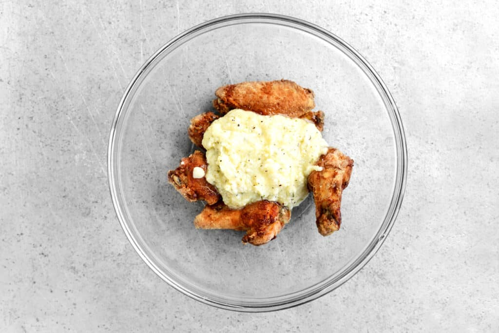 parmesan garlic sauce and cooked chicken wings in a glass bowl