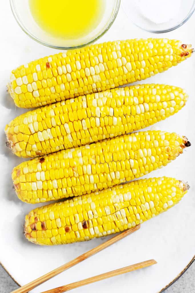 four ears of corn on a white platter with butter and salt