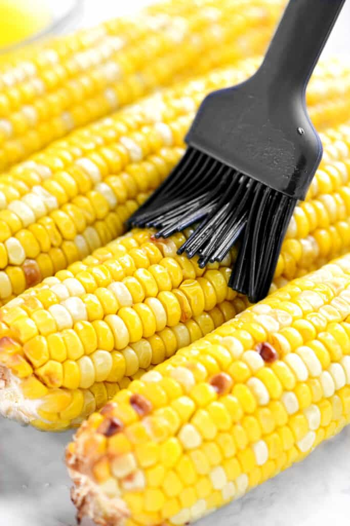 brushing melted butter on cooked corn